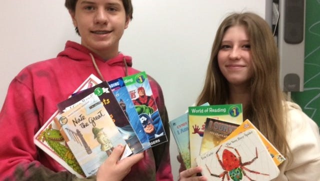 Alex Jaeger and Samantha Baltzell display some of the books collected in D.C. Everest Junior High's book drive.