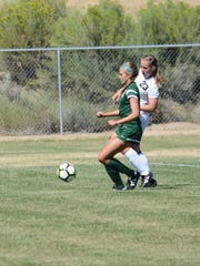 Aztec's Denym Seabolt, right, and Hope Christian's Brenna McGuirk chase after the ball in the first half of Saturday's match at the Aztec soccer complex. The Tigers won, 4-0.