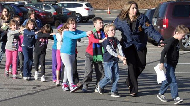 Connecticut State Police lead children from the Sandy Hook Elementary School in Newtown, Conn., following a shooting on Dec. 14, 2012.