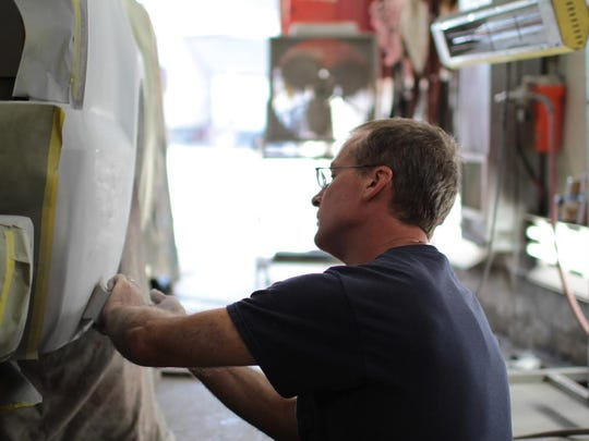 Ray Fetzner sands the primer on a Chevy truck before he is ready for paint. Ray started full time in 1976.
