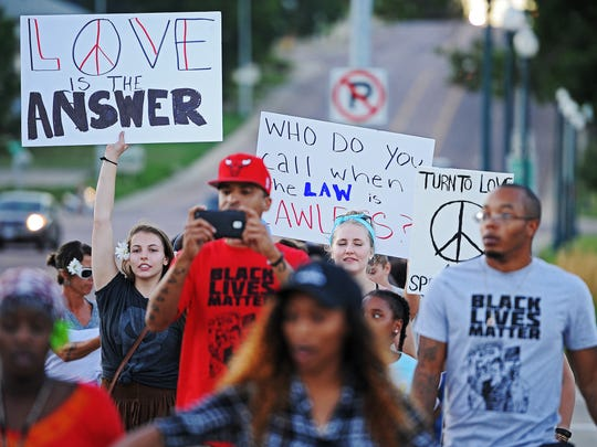 Marchers, including Glory Yount, 17, left, march south