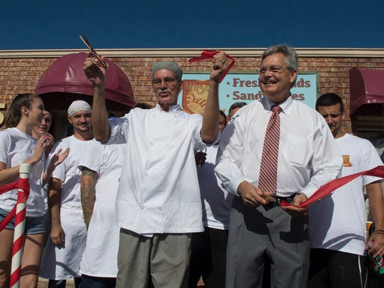 Johnson, left, cuts the opening day ribbon with Fort Myers Mayor Randy Henderson Tuesday. They were accompanied by employees of the bakery.