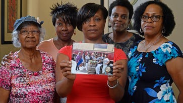 Five members of the Sistahs on the Reading Edge book club, all of Antioch, from left, Katherine Neal, Georgia Lewis, Lisa Renee Johnson, Allisa Carr and Sandra Jamerson stand together at Johnson's home in Antioch, Calif., on Monday, Aug. 24, 2015. The five women were among 11 African-American women who were were booted off the Napa Valley Wine Train on Saturday afternoon. Johnson holds a photograph of the group that was taken before boarding the train.