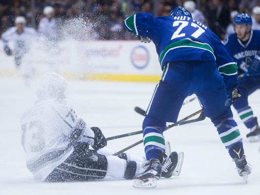 Los Angeles Kings' Tyler Toffoli, left, is dusted after colliding with Vancouver Canucks' Ben Hutton during first-period NHL hockey game action in Vancouver, British Columbia, Friday, March 31, 2017. (Darryl Dyck/The Canadian Press via AP)