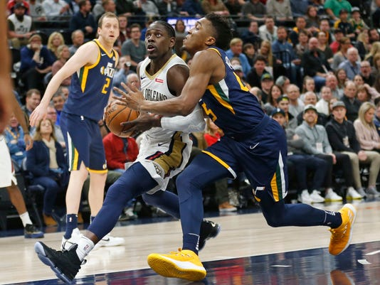 Utah Jazz guard Donovan Mitchell, right, guards New Orleans Pelicans guard Jrue Holiday, left, as he drives to the basket in the first half during an NBA basketball game Wednesday, Jan. 3, 2018, in Salt Lake City. (AP Photo/Rick Bowmer)