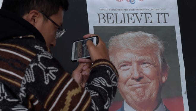 In this Nov. 9 photo, Zheng Gao of Shanghi, China, photographs the front pages of newspapers on display outside the Newseum in Washington, the day after Donald Trump won the presidency. Chinese President Xi Jinping has reaffirmed the importance of relations with the United States in a phone conversation with President-elect Trump. Xi spoke by telephone with Trump on Monday in the first known communication between the two men.