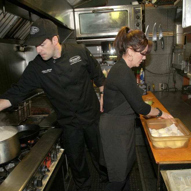 Author and actress Melissa Gilbert prepares biscuits at Diamonds Steak & Seafood in Howell as executive chef Adam Merkel stirs the gravy for Gilbert's item, which will soon be on the menu.