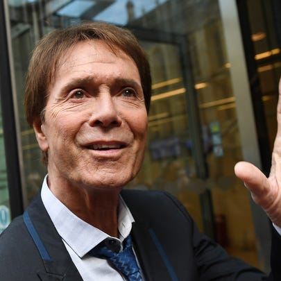 Sir Cliff Richard waves as he arrives at the High Court