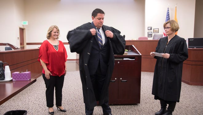Shawna Cole, left, and Chief District Judge Karen Townsend watch as Erich Cole tries on his robe shortly after being sworn in as a magistrate court judge on Friday in Aztec District Court.