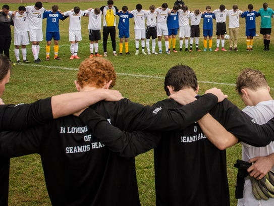Harwood and U-32 soccer players lock arms at midfield