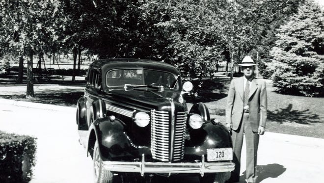 Otero County Sheriff Beacham standing in front of his new 1938 Buick squad car in Alamogordo.