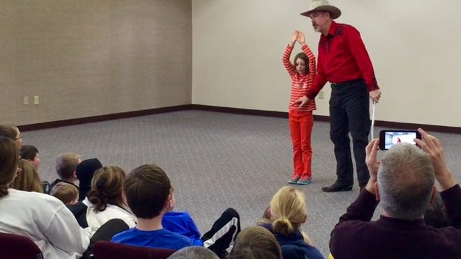 Chris Camp cracks jokes while explaining how he'll demonstrate his whip-cracking skills with the help of 7-year-old volunteer Ella Love on Sunday, Feb. 21, at the Tippecanoe County Public Library in Downtown Lafayette.