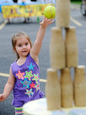 Isbella Cannon, of Mountain Home, takes aim at wooden bottles during last year's Park Pride. The popular event, featuring a number of fun activities for kids, begins at 6 p.m. today.