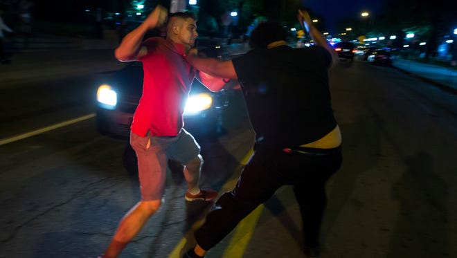 A fight breaks out while a group of demonstrators block an intersection in Ann Arbor, Mich., on Sept. 20, 2017. The demonstrators gathered to protest incidents of racism on campus at the University of Michigan.