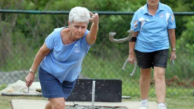 Seven-time world horseshoe champion Joan Elmore, left, pitched 28 ringers in a 30-pitch qualifying round against Joann Stanford on Saturday.