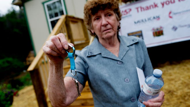 Glenna Ogle holds the keys to her new home during the house dedication ceremony for Glenna Ogle, who lost her home during the November 28 wildfires in Gatlinburg, Tennessee on Friday, July 28, 2017. The home is the first of 25 homes to be built for fire victims by Appalachia Service Project.