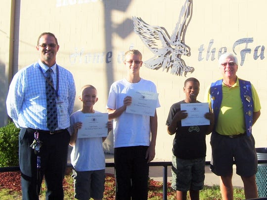 Sixth grader Logan Wright, seventh grader Jalen Horton and eighth grader McKae Tieman were recognized as the most improved students this month by Holloman Middle School Principal Steven Starkovich (left) and Kiwanas member Ned Kline (right).