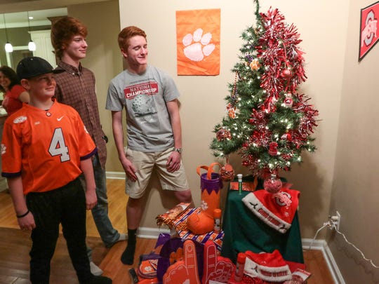 From left, Derrick Merlo, Chris Merlo and Brent Merlo look at a football-themed Christmas tree Friday in their living room in Anderson.