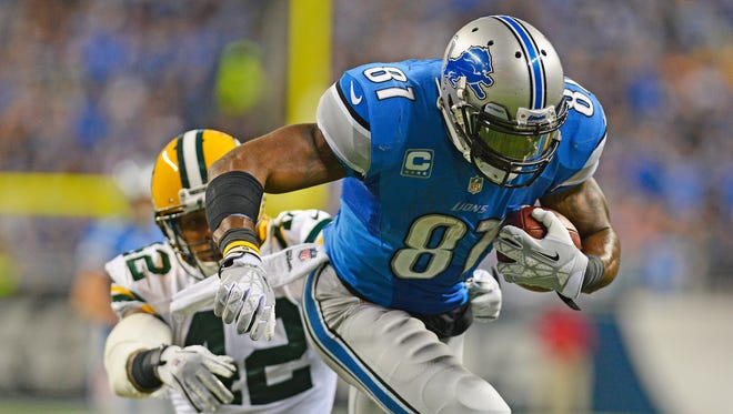 Morgan Burnett of the Packers whiffs on a tackle attempt as Lions receiver Calvin Johnson heads for the end zone at Ford Field in Detroit.