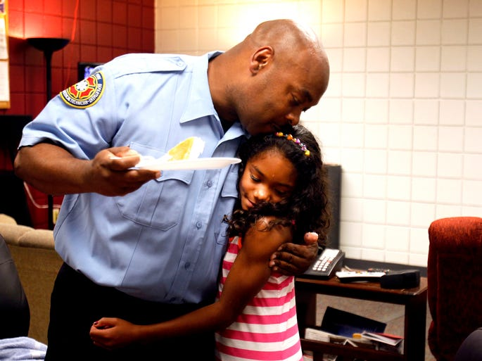 Kevin Gill hugs and gives a kiss to Mya Roberts, 9,  during a reunion eight years in the making at the Indianapolis Fire Department Station 1 in Indianapolis on Sunday, Aug. 10, 2014. Indianapolis Firefighter Private Gill responded to a house fire in 2006 and saved the life of then 8-month-old Mya Roberts.