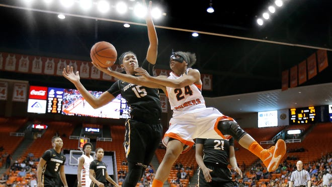 UTEP guard Jenzel Nash contorts herself around Southern Miss defender Caitlin Jenkins during their conference game Thursday at the Don Haskins Center.