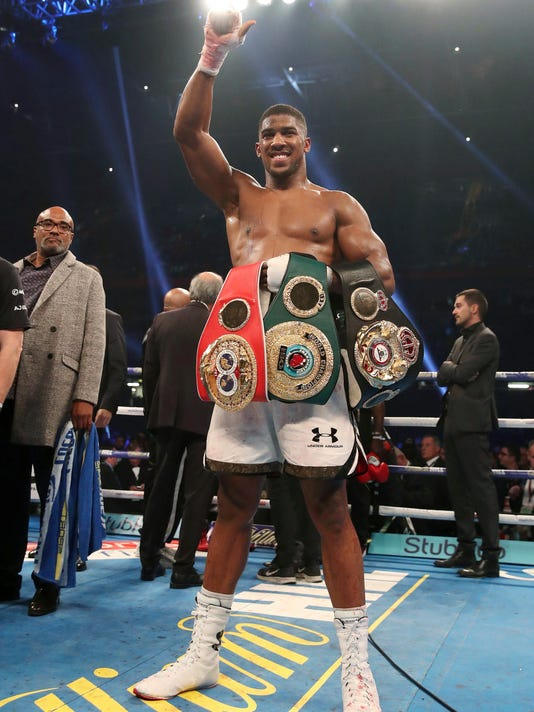 Anthony Joshua celebrates victory over Carlos Takam after the IBF World Heavyweight Title, IBO World Heavyweight Title and WBA Super World Heavyweight Title bout at the Principality Stadium, Cardiff, Wales, Saturday, Oct. 28, 2017. (Nick Potts/PA via AP)