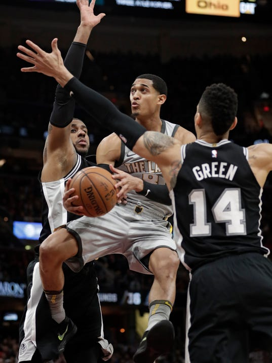 Cleveland Cavaliers' Jordan Clarkson, center, drives to the basket against San Antonio Spurs' LaMarcus Aldridge, left, and San Antonio Spurs' Danny Green in the second half of an NBA basketball game, Sunday, Feb. 25, 2018, in Cleveland. The Spurs won 110-94. (AP Photo/Tony Dejak)