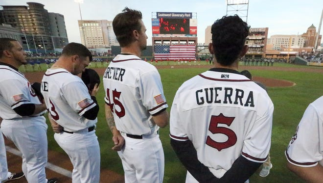 El Paso Chihuahuas stand as a large U.S. flag is unfurled in the outfield at the start of their home opener of their 5th season Tuesday at Southwest University Park. They took on the Salt Lake Bees.