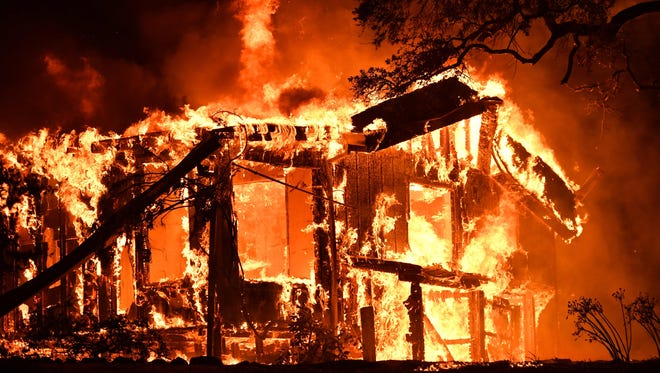 Flames ravage a home in the Napa wine region in California on Oct. 9, 2017.