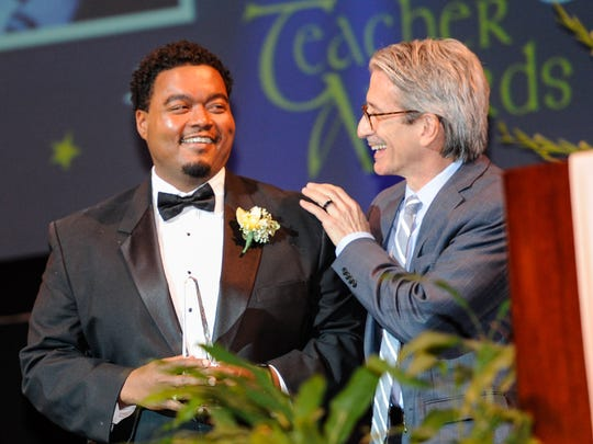 James Flachsenhaar presents Vincent Robert Hicks, who teaches 6th and 8th grade health and Physical Education at David Thibodaux STEM Magnet School with award for Teacher of the Year in the middle school category at the Lafayette Education Foundation awards ceremony Wednesday.