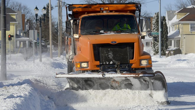A City of Lansing snow plow runs down Allegan Street last winter.