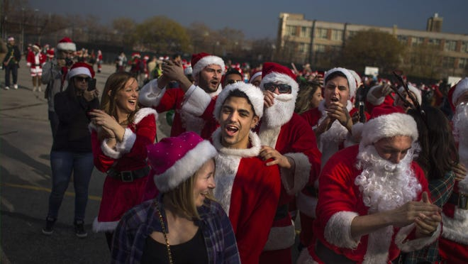 Revelers dressed in holiday-themed costumes sing as they participate in SantaCon in New York on Saturday.