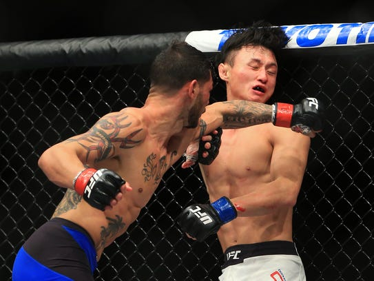 Cub Swanson (L) throws a punch at Doo Ho Choi in their