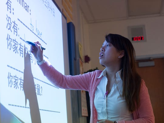 Quynh Nguyen writes Mandarin characters on a smart board during Mandarin Chinese class at Brimm Medical Arts High School in Camden.