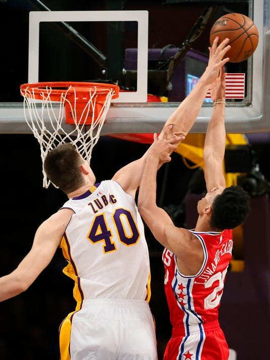 Los Angeles Lakers center Ivica Zubac, left, blocks a shot by Philadelphia 76ers guard Timothe Luwawu-Cabarrot, right, during the first half of an NBA basketball game, Sunday, March 12, 2017, in Los Angeles. (AP Photo/Danny Moloshok)