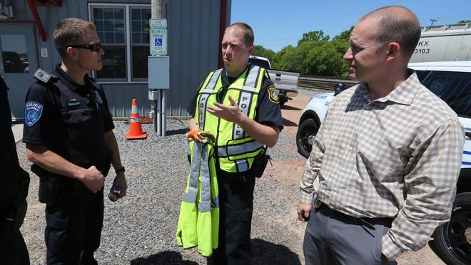"""Marshfield Police Officer Jamie Kizer, left, and Police Chief Rick Gramza, right, listen to Canadian National special agent Russ Kollmansberger at a railroad safety event Monday in Marshfield called """"The Officer on the Train."""" Kizer was the officer who got to ride in a Canadian National locomotive to check out safety issues in the Marshfield area."""