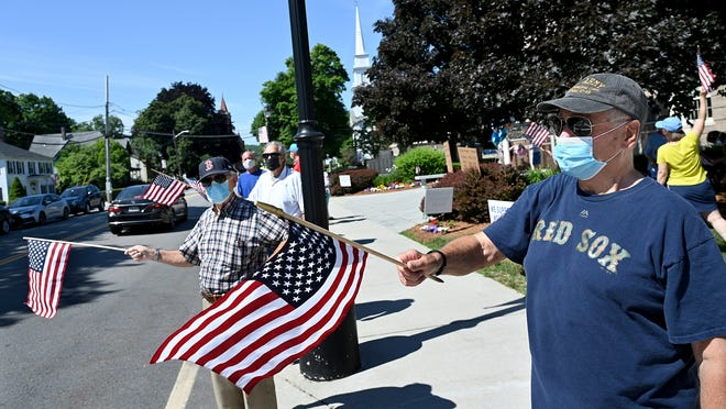 Ken Gagnon, right, of Westborough, and others wave American flags during a rally Saturday in support of police outside the Westborough Police Department headquarters.