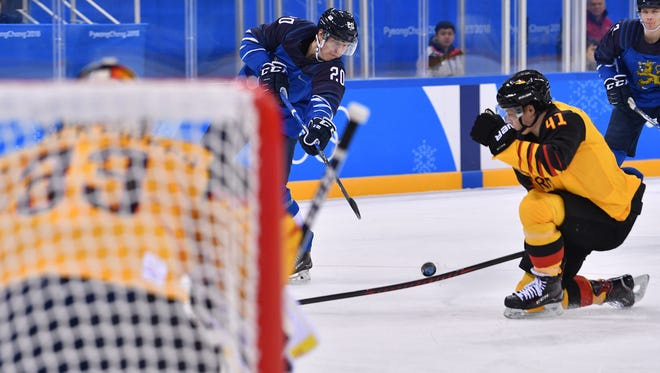 Feb 15, 2018; Gangneung, South Korea; Finland forward Eeli Tolvanen (20) shoots the puck as Germany defenseman Jonas Muller (41) drops to try and block it in a hockey game between Finland and Germany during the Pyeongchang 2018 Olympic Winter Games at Gangneung Hockey Centre. Mandatory Credit: Andrew Nelles-USA TODAY Sports