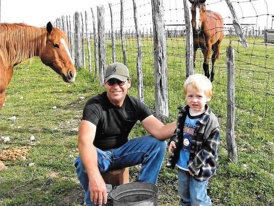Mike Davis shows horses to his grandson Brayden Leverett.