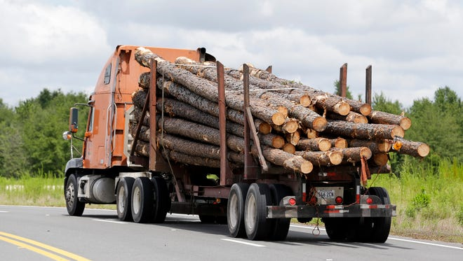 """To help avoid crashes, Mississippi law requires log trucks to mark their cargo """"overhang"""" from the back of the truck. The longest log must be marked with a red flag during the day and an amber or red flashing light at night."""