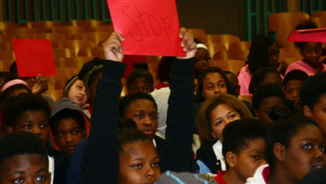"""Alexandria Middle Magnet School held an anti-bullying rally on Thursday. Students were given signs with the word """"Stop"""" on them and were told to hold up the signs to stop bullying when portrayed in a skit."""