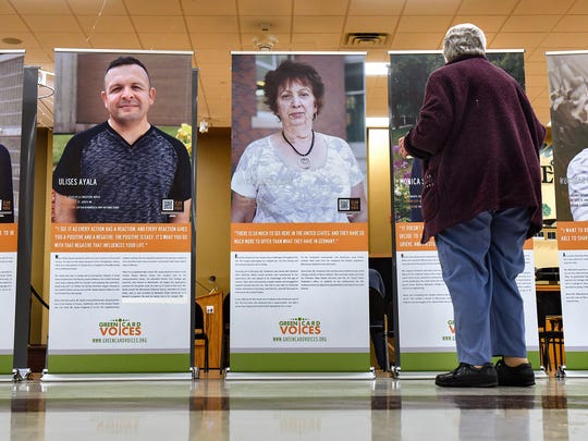 People view the Green Card Voices exhibit at the Whitney Senior Center in St. Cloud.