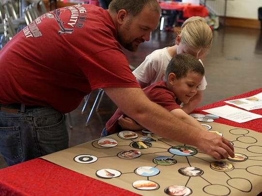Eldon King helps his children, Michael and Makayla, work on an agricultural activity during the San Angelo Museum of Fine Arts'  Family Day Tall Tales event Saturday, March 11, 2017.
