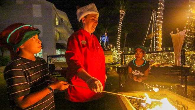 Zachary Yoshida, 10, and friend, Olivia Parmeley, 8, get help from Heather Miltner, a cook at South Seas Island Resort, to roast their marshmallows for s'mores at last December's holiday stroll in conjunction with the Captiva Holiday Village. This year's holiday stroll will be Friday and Saturday nights beginning Dec. 9 and ending Dec. 24.