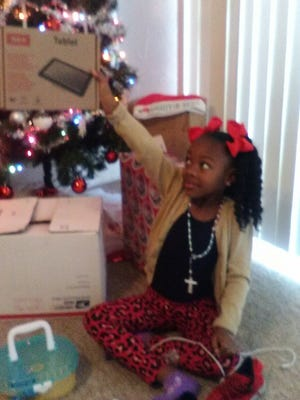 Kéani Page of Lafayette, names Princess for a Day by the New Orleans Pelicans, opens Christmas presents.