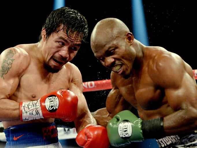 Timothy Bradley Jr.(brown gloves) and Manny Pacquiao (red gloves) during their WBO World Welterweight Championship fight at MGM Grand Garden Arena.