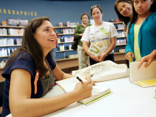 "Author Diana Lopez signs copies of her book, ""Confetti"