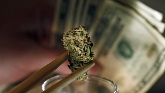 A caregiver picks out a marijuana bud for a patient at a marijuana dispensary in Denver on Sept. 18, 2012.