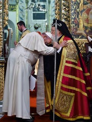 In this photo provided by Vatican newspaper L'Osservatore Romano, Ecumenical Patriarch Bartholomew I, right, kisses Pope Francis' head during an ecumenical prayer at the Patriarchal Church of St. George in Istanbul, Saturday, Nov. 29, 2014. The two major branches of Christianity represented by Bartholomew and Francis split in 1054 over differences on the power of the papacy. The two spiritual heads will participate in an ecumenical liturgy and sign a joint declaration in the ongoing attempt to reunite the churches.