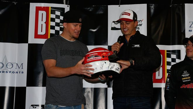 IndyCar driver Graham Rahal (right) gives actor and Honda Indy Grand Prix of Alabama grand marshal Channing Tatum a helmet signed by IndyCar drivers.